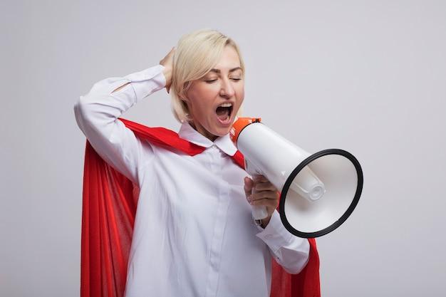 Blonde superheldenvrouw van middelbare leeftijd in een rode cape die in een luidspreker schreeuwt en naar beneden kijkt terwijl ze de hand op het hoofd houdt