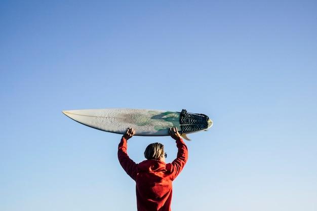 Blonde surfer van achteren neemt de surftafel op zijn hoofd