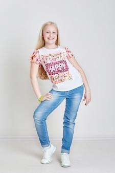 Blonde tiener van het meisje in jeans en een t-shirt