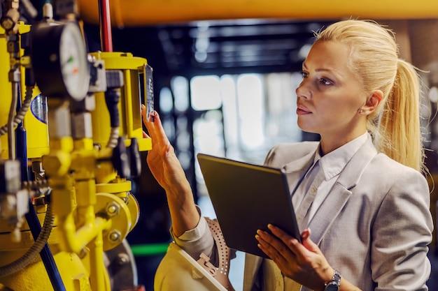 Blonde toegewijde succesvolle zakenvrouw in formele slijtage die machines controleert en tablet vasthoudt terwijl hij in een elektriciteitscentrale staat