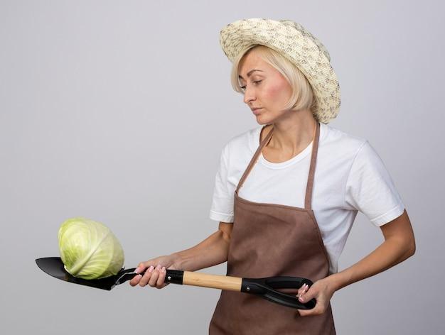 Blonde tuinmanvrouw van middelbare leeftijd in uniform met een hoed die in profielweergave staat en een schop vasthoudt met kool erop en naar kool kijkt