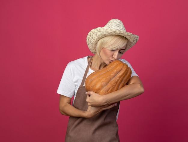 Blonde tuinmanvrouw van middelbare leeftijd in uniform met een hoed die naar butternut-pompoen kijkt en kust