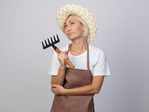Blonde tuinmanvrouw van middelbare leeftijd in uniform met een hoed met een hark die de hand op de elleboog houdt en omhoog kijkt