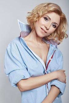 Blonde van de portret het sexy bedrijfsvrouw in blauw overhemd