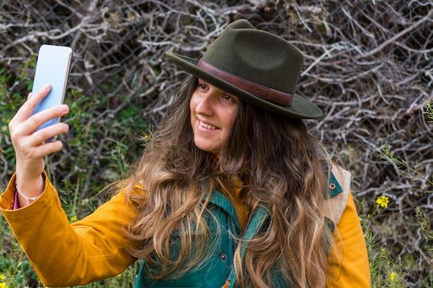 Blonde verkenner. ze draagt een groen vest en een groene hoed en maakt een foto met haar mobiele telefoon. digitale nomade.