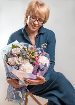 Blonde verouderd met mooi boeket bloemen. een dame in blauwe gebreide jumpsuit zit op een stoel. moederdag verjaardag