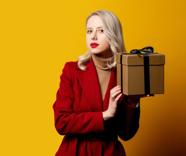Blonde verraste vrouw in rode jas met giftdoos op gele muur