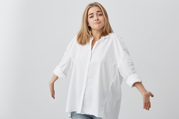 Blonde verwarde blanke vrouw in wit overhemd schouderophalend, armen naar voren strekkend, starend met een twijfelachtige en clueless blik, zeggend dat ik het niet weet. mensen en emoties concept.