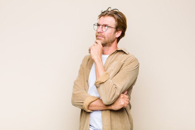 Blonde volwassen blanke man die nadenkend voelt, ideeën afvraagt of verbeeldt, dagdroomt en opkijkt om ruimte te kopiëren
