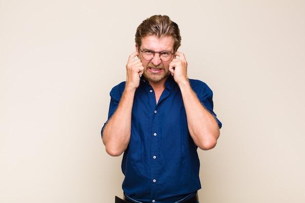 Blonde volwassen blanke man kijkt boos, gestrest en geïrriteerd, beide oren bedekt met een oorverdovend geluid, geluid of luide muziek