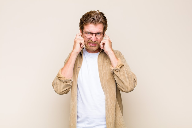 Blonde volwassen blanke man kijkt boos, gestrest en geïrriteerd en bedekt beide oren met een oorverdovend geluid, geluid of luide muziek