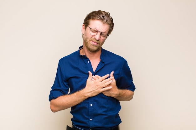 Blonde volwassen blanke man kijkt verdrietig, gekwetst en diepbedroefd, houdt beide handen dicht bij het hart, huilt en voelt zich depressief