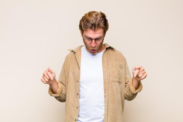 Blonde volwassen blanke man voelt geschokt, met open mond en verbaasd, kijkt en wijst naar beneden in ongeloof en verbazing
