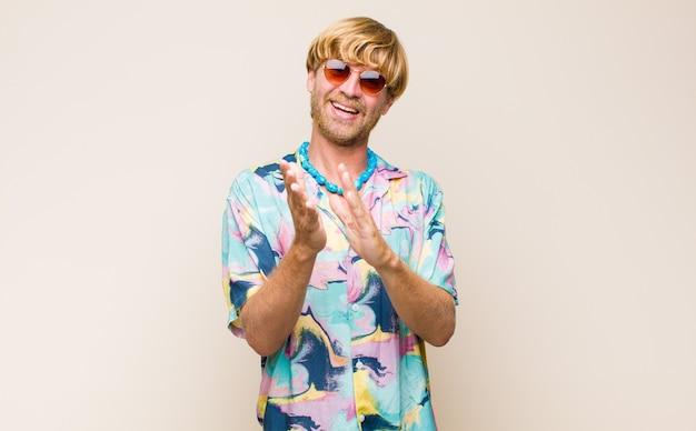 Blonde volwassen blanke man voelt zich gelukkig en succesvol, lacht en klapt in de handen, zegt gefeliciteerd met een applaus
