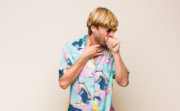 Blonde volwassen blanke man ziek met keelpijn en griepsymptomen, hoesten met bedekte mond