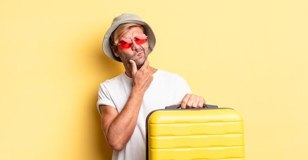 Blonde volwassen man denken, twijfelachtig en verward voelen. reiziger concept