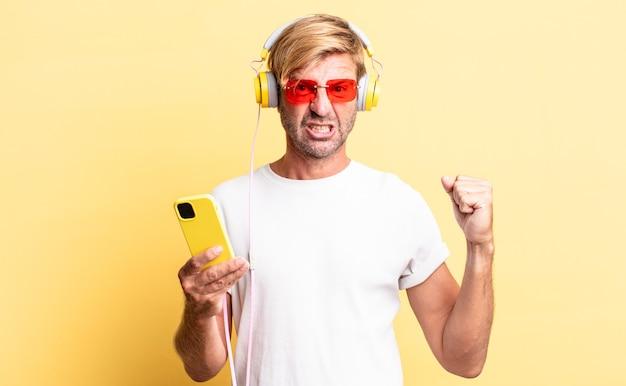 Blonde volwassen man die agressief schreeuwt met een boze uitdrukking met een koptelefoon
