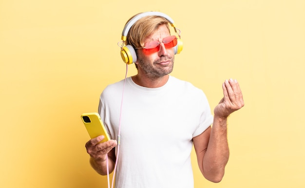 Blonde volwassen man die capice of geldgebaar maakt en zegt dat je met een koptelefoon moet betalen
