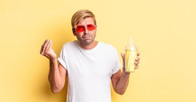 Blonde volwassen man die capice of geldgebaar maakt en zegt dat je met een milkshake moet betalen