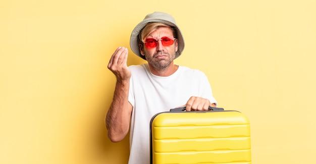 Blonde volwassen man die capice of geldgebaar maakt en zegt dat je moet betalen. reiziger concept