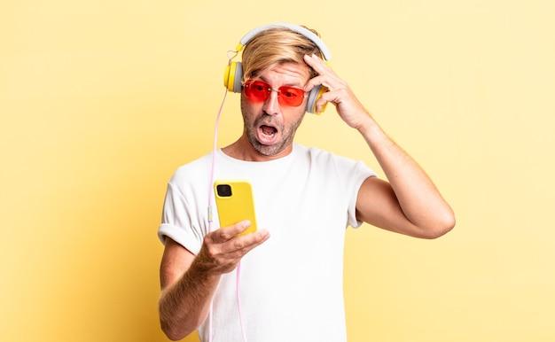 Blonde volwassen man die er blij, verbaasd en verrast uitziet met een koptelefoon