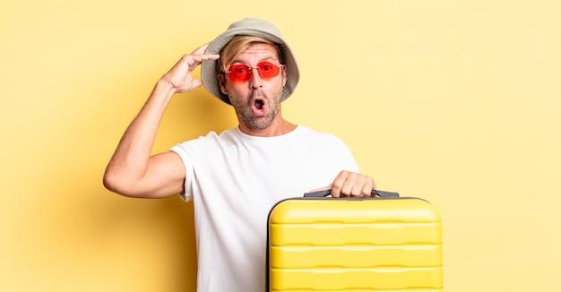 Blonde volwassen man die er blij, verbaasd en verrast uitziet. reiziger concept