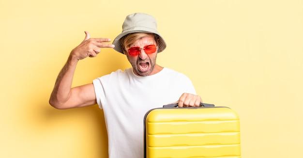 Blonde volwassen man die er ongelukkig en gestrest uitziet, zelfmoordgebaar dat een pistoolteken maakt. reiziger concept