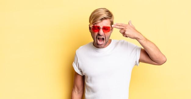 Blonde volwassen man die er ongelukkig en gestrest uitziet, zelfmoordgebaar maakt een pistoolteken en een zonnebril draagt