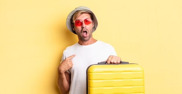 Blonde volwassen man die geschokt en verrast kijkt met wijd open mond, wijzend naar zichzelf. reiziger concept
