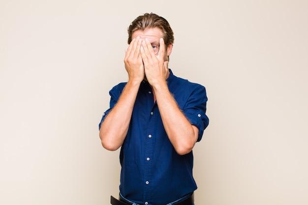 Blonde volwassen man die gezicht bedekt met handen, met verbaasde uitdrukking tussen vingers gluurt en naar de zijkant kijkt
