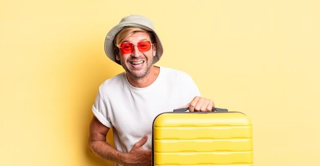 Blonde volwassen man die hardop lacht om een hilarische grap. reiziger concept