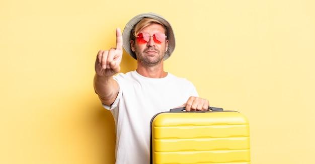 Blonde volwassen man die lacht en er vriendelijk uitziet, met nummer één. reiziger concept