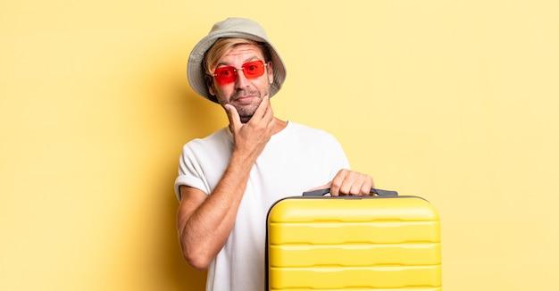 Blonde volwassen man die lacht met een vrolijke, zelfverzekerde uitdrukking met de hand op de kin. reiziger concept