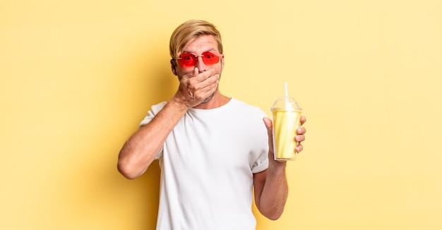 Blonde volwassen man die mond bedekt met handen met een schok met een milkshake