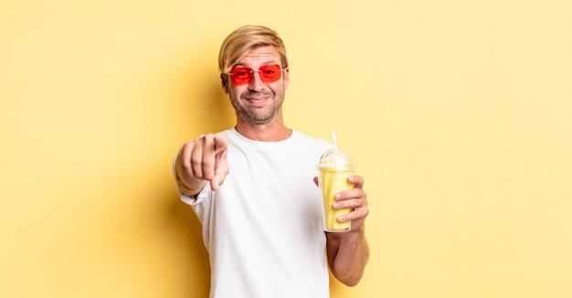Blonde volwassen man die naar de camera wijst en jou kiest met een milkshake