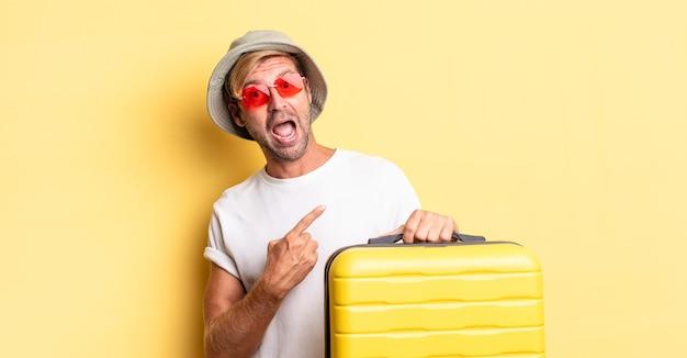 Blonde volwassen man die opgewonden en verrast kijkt en naar de zijkant wijst. reiziger concept
