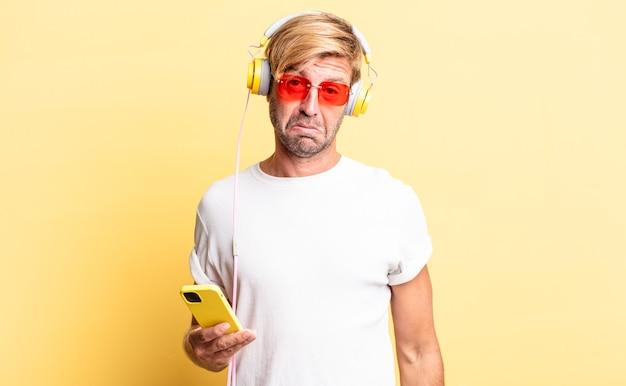Blonde volwassen man die verbaasd en verward kijkt met een koptelefoon