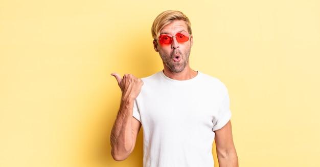 Blonde volwassen man die verbaasd kijkt in ongeloof en een zonnebril draagt