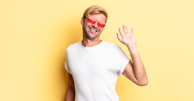 Blonde volwassen man die vrolijk lacht, met de hand zwaait, je verwelkomt en begroet en een zonnebril draagt