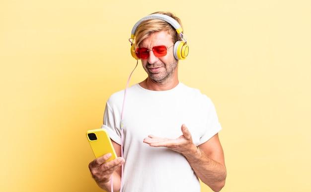 Blonde volwassen man die vrolijk lacht, zich gelukkig voelt en een concept met een koptelefoon laat zien