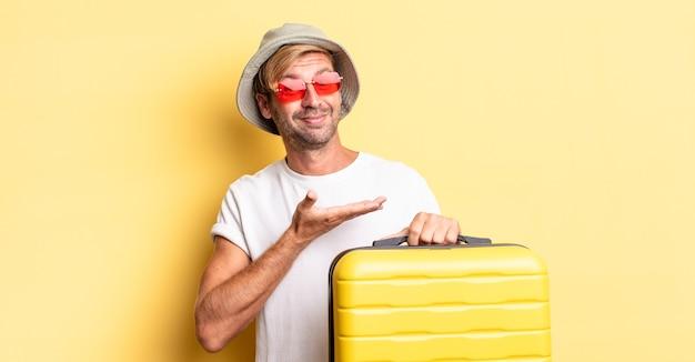 Blonde volwassen man die vrolijk lacht, zich gelukkig voelt en een concept toont. reiziger concept