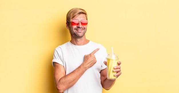 Blonde volwassen man die vrolijk lacht, zich gelukkig voelt en naar de zijkant wijst met een milkshake