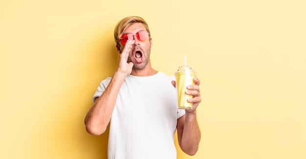 Blonde volwassen man die zich gelukkig voelt, een grote schreeuw geeft met de handen naast de mond met een milkshake