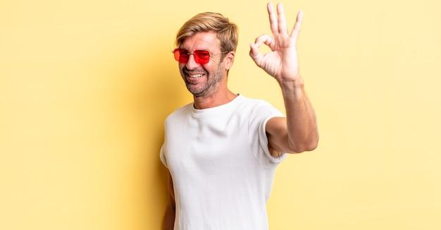Blonde volwassen man die zich gelukkig voelt, goedkeuring toont met een goed gebaar en een zonnebril draagt
