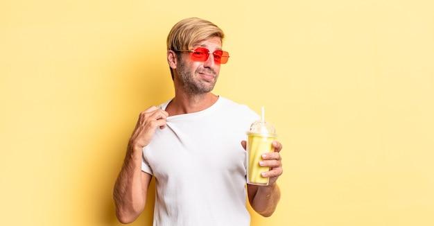 Blonde volwassen man die zich gestrest, angstig, moe en gefrustreerd voelt met een milkshake
