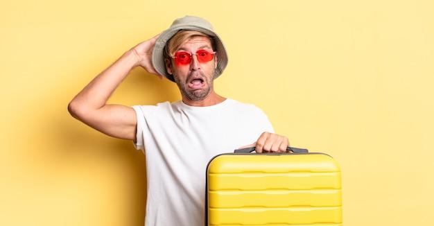 Blonde volwassen man die zich gestrest, angstig of bang voelt, met de handen op het hoofd. reiziger concept