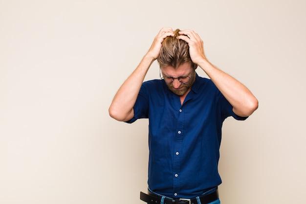 Blonde volwassen man die zich gestrest en gefrustreerd voelt, zijn handen opheft naar het hoofd, zich moe, ongelukkig en met migraine voelt