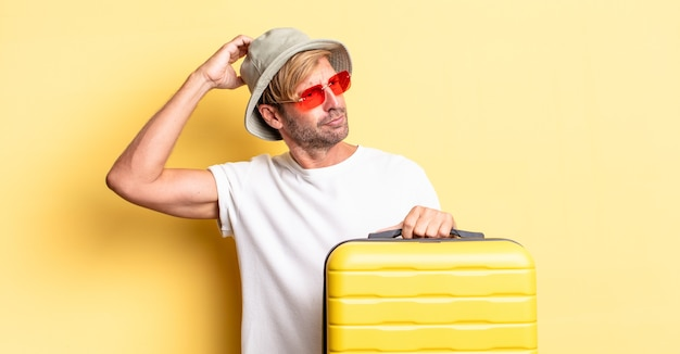 Blonde volwassen man die zich verbaasd en verward voelt, hoofd krabben. reiziger concept