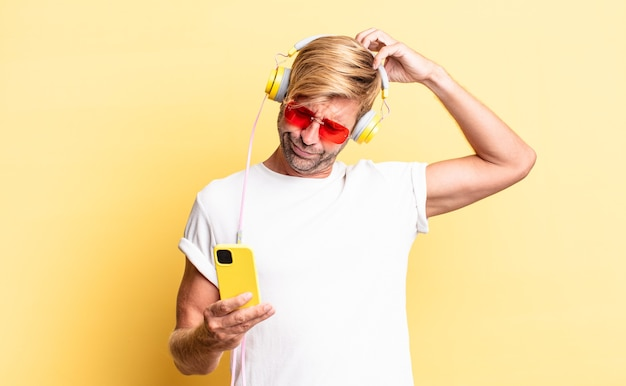 Blonde volwassen man die zich verbaasd en verward voelt, hoofd krabbend met een koptelefoon