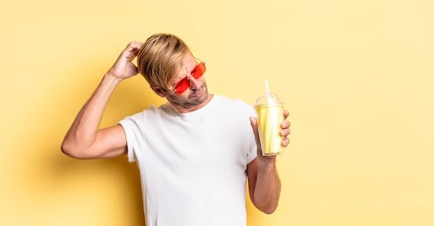 Blonde volwassen man die zich verward en verward voelt, hoofd krabben met een milkshake